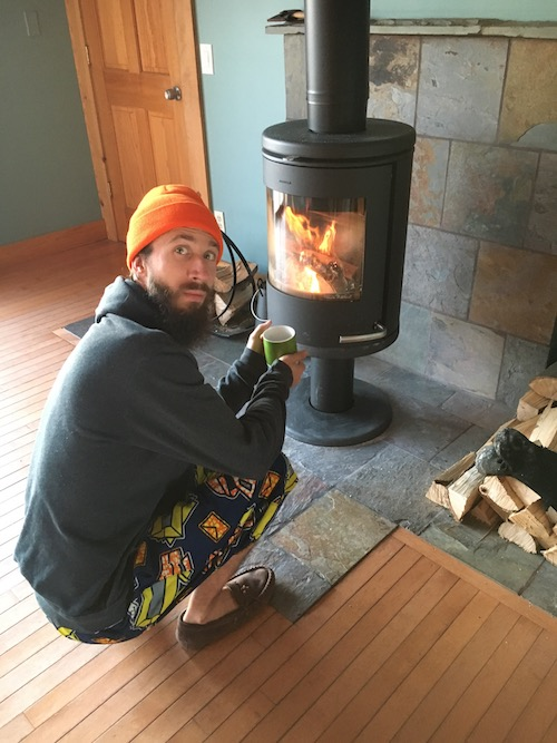 a photo of me with coffee by a wood fire